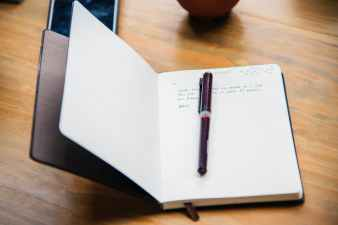 black and blue plastic pen non top of black covered notebook